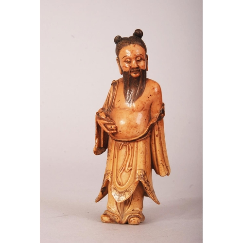 60 - C17th/18th Chinese carved soapstone figure of an immortal, shown standing and wearing loose robes re...