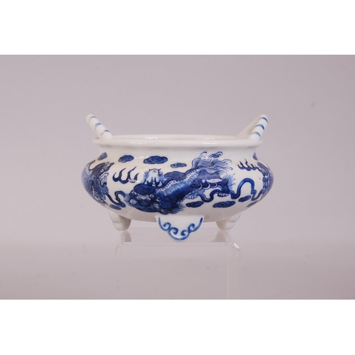 16 - C19th Chinese blue and white tripod censer, painted with four lions at play, two loop handles rise f...