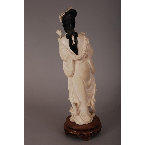 55 - C19th Chinese carved ivory figure of a lady, holding a flower spray and wearing long robes, wood sta...