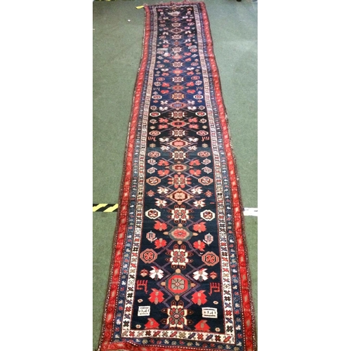 57 - Rug - runner in reds, blue & cream borders with blue centre 488x92cm...