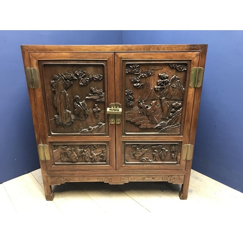 26 - A Chinese Late C19th hardwood cabinet with carved figural panels, opening to reveal 2 drawers & shel...