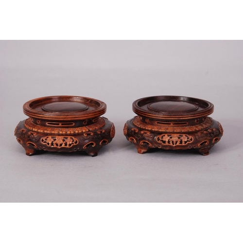 34 - A pair of Chinese carved wood circular stands (2)...