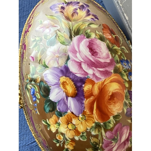 35 - A hand painted and hinged opening ceramic porcelain egg with French stamp to base, brass bound and f...