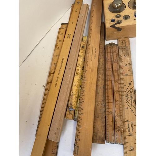 49 - Qty of vintage measuring rulers, sticks, some Boxwood,  a wooden set of brass gram weights (some mis...
