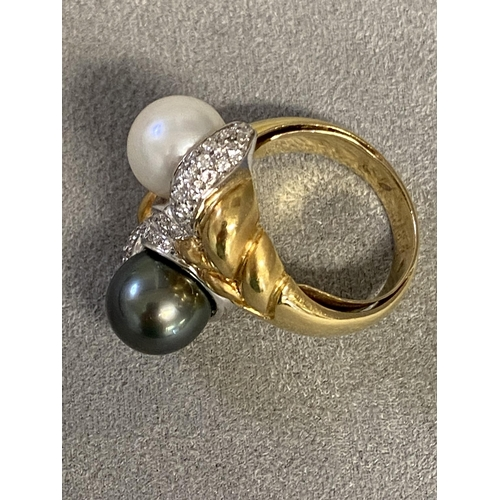 1 - An  impressive 18ct gold black and white pearl cross over ring, with central band of platinum mounte...