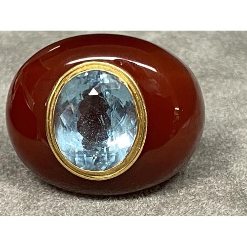 23 - Aqua marine, carnelian and yellow metal ladies dress ring, centrally set with oval free cut aqua mar...