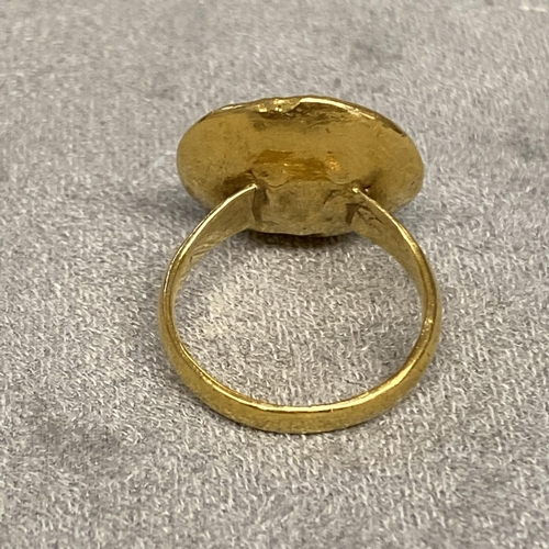24 - Unmarked yellow metal seal ring, with carved gem set intaglio of a classical bust, 6.1 g size L. Som...