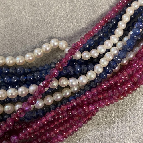 36 - A triple stand necklace of cabochon ruby, sapphires and seed pearls, on a pearl set 14ct white gold ...