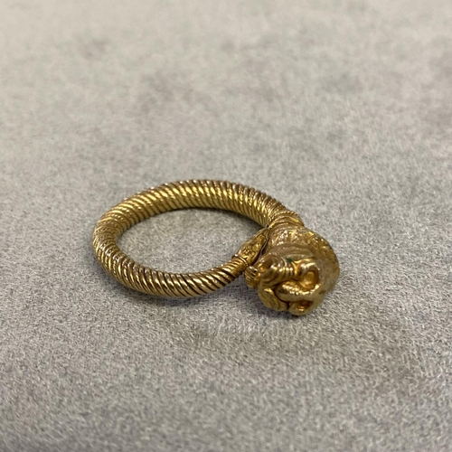 34 - Unmarked yellow metal coil ring with lions head finial, 8.5grams, size M