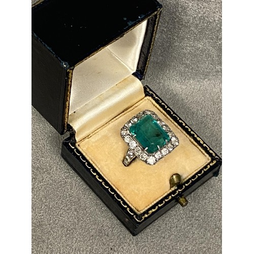 9 - A platinum diamond and emerald ladies dress ring, central 5 ct emerald in 8 claw setting, with a sur...