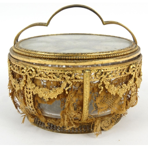 16 - French pierced gilt metal and glass powder bowl with bow and swag design inset with lace, 15cm tall...