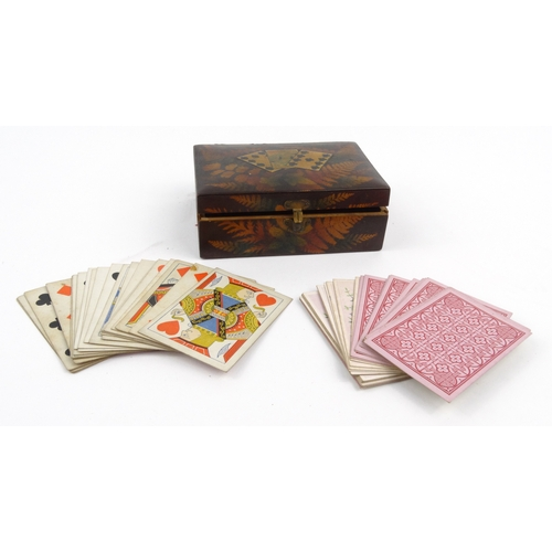 55 - Victorian fern work wooden card box with a selection of playing cards, 15cm diameter...
