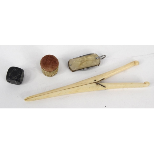 145 - Group of sewing items comprising needlecase book, advertising penknife, bone pin cushion, bone glove...