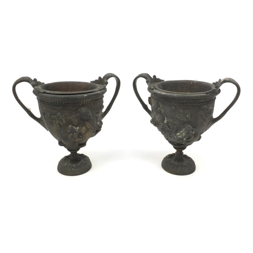 37 - Pair of brass twin handled urns both embossed with classical scenes, both with liners, each 16cm hig...