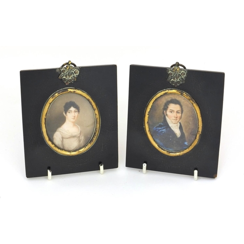 16 - Pair of 19th century oval portrait miniatures, one of a gentleman wearing a blue coat, the other of ...