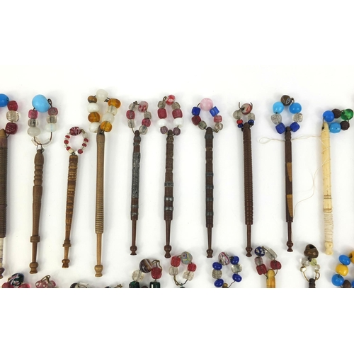 42 - Collection of sewing interest wooden and bone bobbins, mostly with glass beads, the largest approxim...