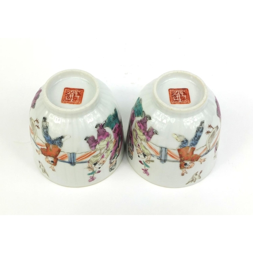 364 - Pair of Chinese porcelain tea cups painted in the famille rose palette with court figures playing, f...