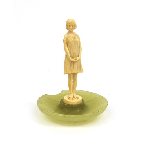 632 - Art Deco carved ivory figure of a young girl wearing a dress, raised on a circular onyx base, inscri...