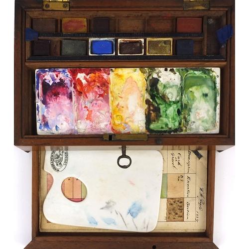 38 - Winsor & Newton Mahogany artists box housing paints and a ceramic palette, 7cm high x 21.5cm wide x ...