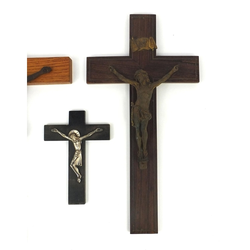 21 - Four religious interest crucifix, including a gilt bronze example mounted on a rosewood crucifix, th...