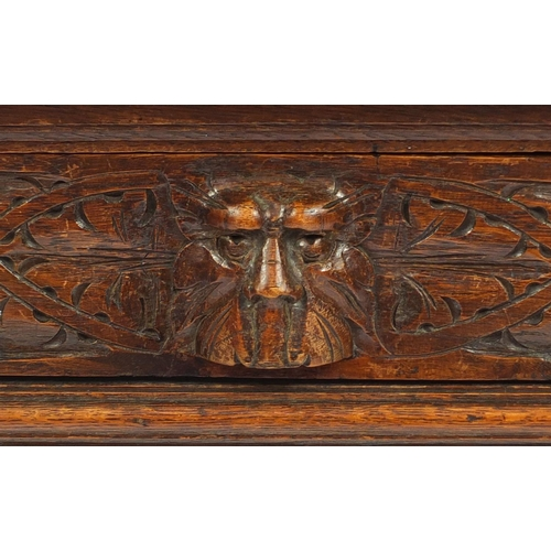 2059 - Victorian oak hall table with tooled leather insert and frieze drawer, carved with grotesque faces a...