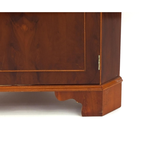 2030 - Yew corner cabinet fitted with two open shelves above a cupboard door, raised on bracket feet, 179cm...