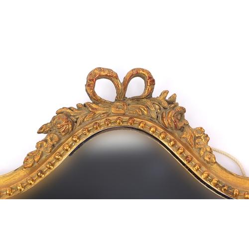 2032 - Gilt framed shield shaped mirror with ribbon crest, 48cm x 31cm