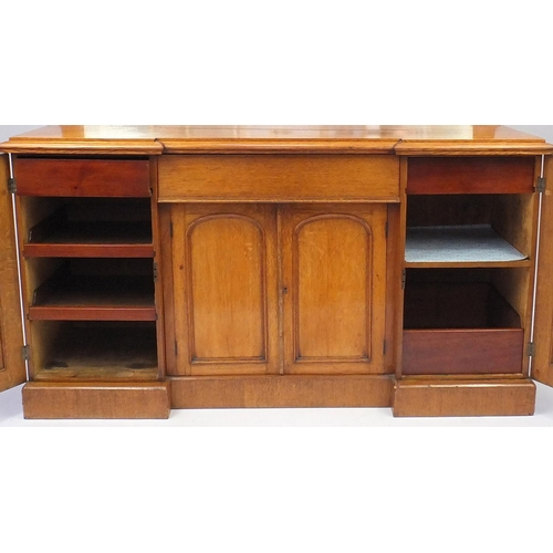 2010 - Victorian oak inverted breakfront sideboard with mirrored back, centre drawer aand four paneled cupb...
