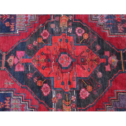 2013 - Rectangular Bakhtiari rug with an all over floral design within geometric floral borders onto a red ...