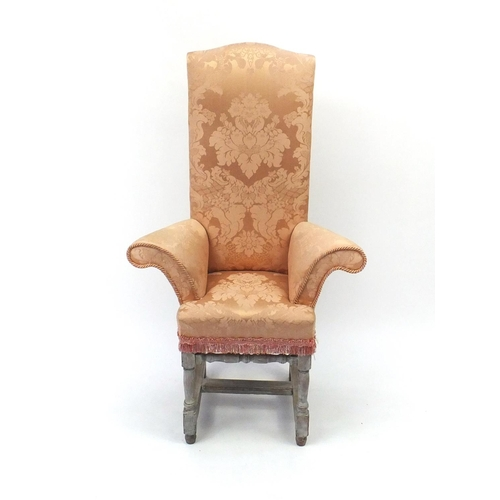 2058 - Bleached wooden framed child's correction chair with outswept arms and peach upholstery, 110cm high