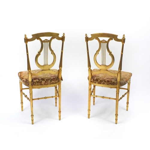 2021 - Pair of Regency gilt wooden side chairs with lyre backs and upholstered stuffover seats