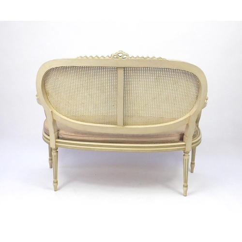 2011 - Cream and green painted two seater salon settee with cane panel back and seat, 103cm high x 120cm wi...