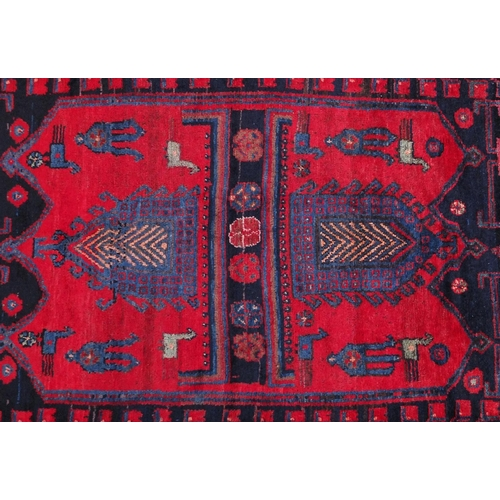 2055 - Rectangular Baluchi rug decorated with animal and floral motifs onto a red and dark blue ground, 230...