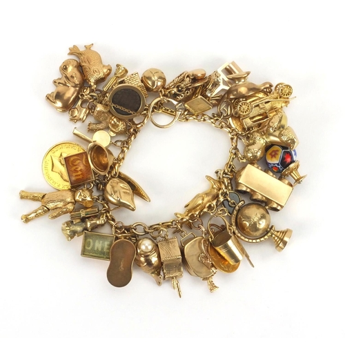 898 - Good 9ct gold charm bracelet with approximately forty mostly gold charms, including two full soverei...