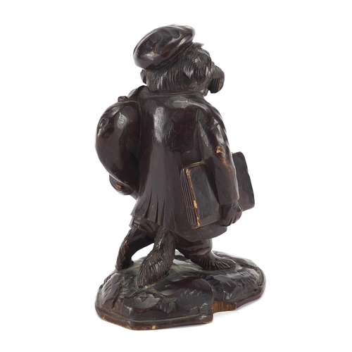 46 - Black forest desk thermometer carved in the form of a dog holding a trombone, 13cm high...