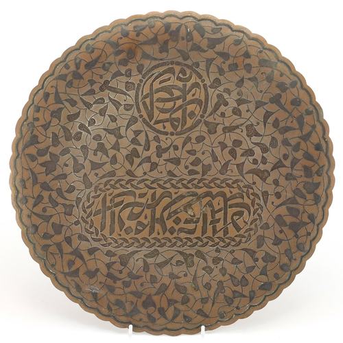 583 - Cairoware brass three footed dish, with silver inlay decorated with script amongst stylised foliage,...
