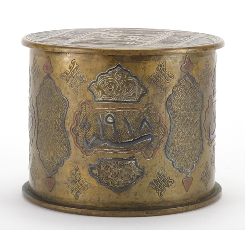 584 - Early 20th century Cairoware cylindrical brass pot and cover with silver inlay, decorated with scrip...