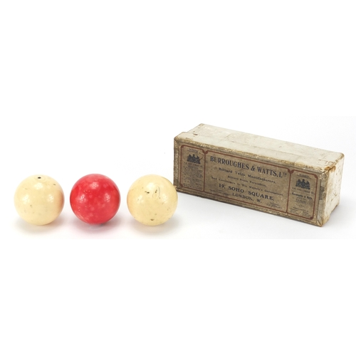 15 - Three turned ivory billiard balls including one stained red, housed in a Burroughes & Watts Ltd, eac...