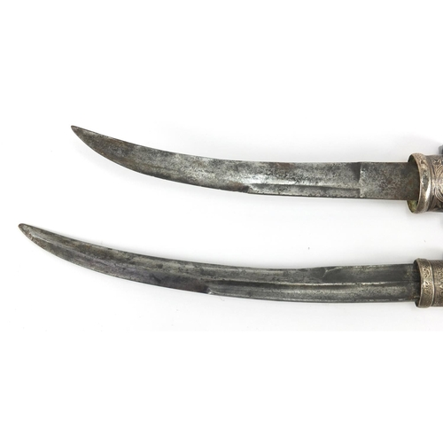 588 - Two Islamic daggers with brass sheaths having silver inlay, engraved with stylised scrolls, the larg...