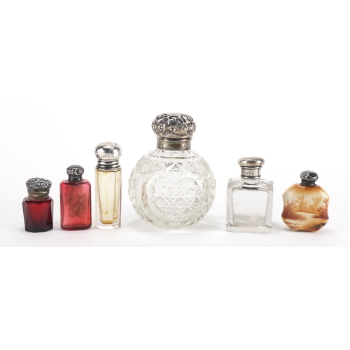 9 - Six silver mounted scent bottles including a globular cut glass example and two faceted ruby example...