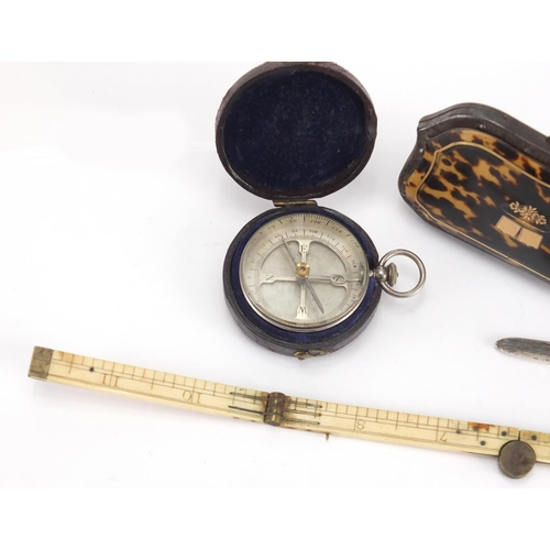 34 - Antique objects comprising a pocket compass with leather case, folding ivory rule, silver bladed mot...