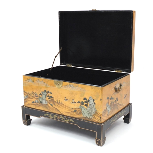 2008 - Chinese lacquered chest with twin handles on stand, hand painted with figures and a river landscape,...