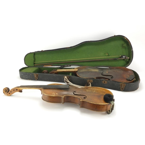 26 - Two old wooden violins, one with bow and carrying case, one violin with one piece back the other bea...