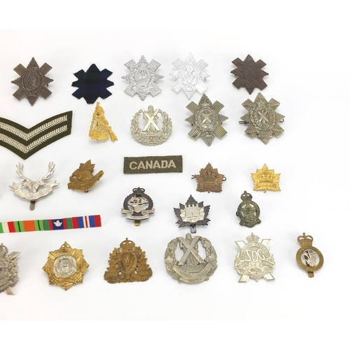 217 - Military interest cap badges and cloth patches including The Cameron Highlanders, British American a...