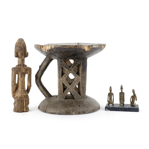 472 - Tribal art comprising a Dogon carved wood figure, three bronze figures raised on a rectangular black...