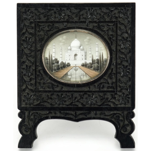 459 - Indian oval miniature finely hand painted with The Taj Mahal, housed in an ebony easel frame carved ...