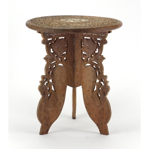 42 - Indonesian carved folding occasional table, with bone inlay, 35cm high x 30cm in diameter...