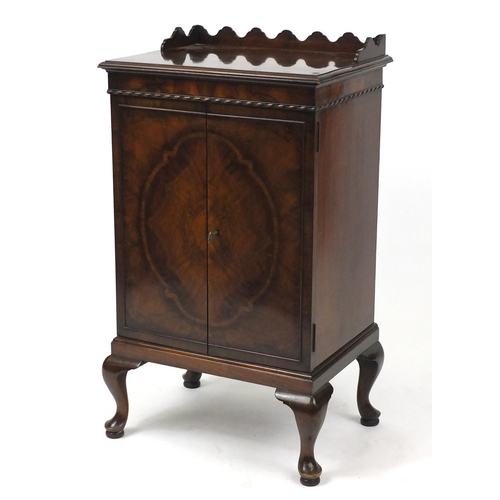 2007 - Waring & Gillow Ltd walnut music cabinet, the mechanical action doors with quarter veneer, raised on...