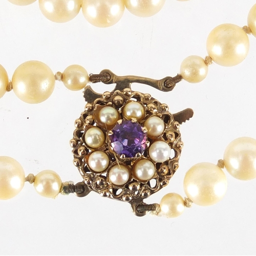 2335 - Simulated pearl two string necklace, with 9ct gold amethyst clasp, 44cm in length, approximate weigh...