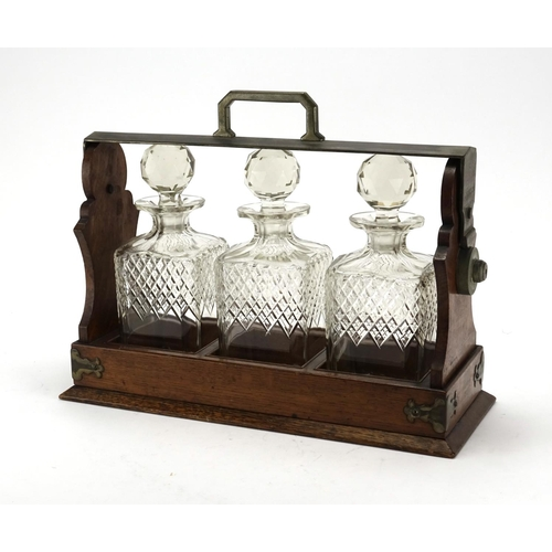 2034 - Oak tantalus with silver plated mounts, housing three glass decanters, retailed by Jay's of Oxford S...